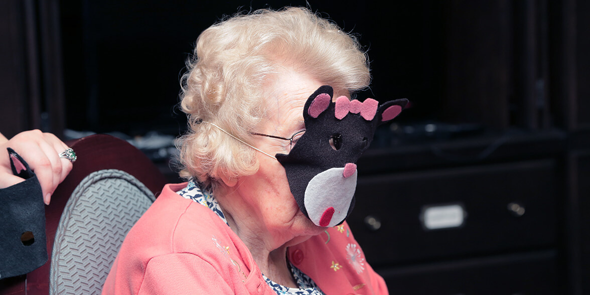 Assisted living resident in character mask